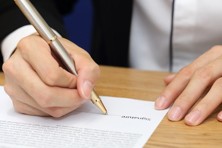 close-up on a businessman hand signing a contract paper Stock Photo