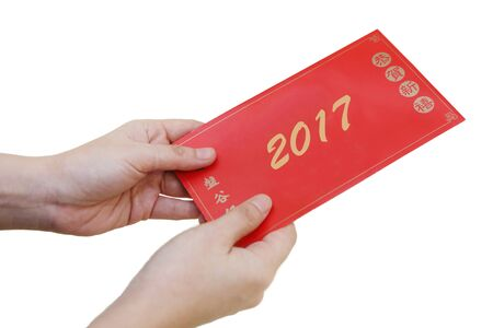 pow: Chinese New Year concept of hand holding ang pow or red envelope with money inside