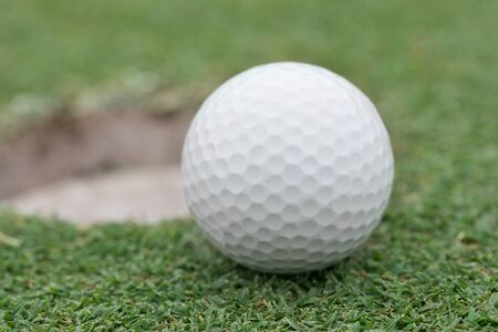 caddie: close-up on a golf ball on lip of cup Stock Photo