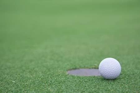 background of golf ball on lip of cup