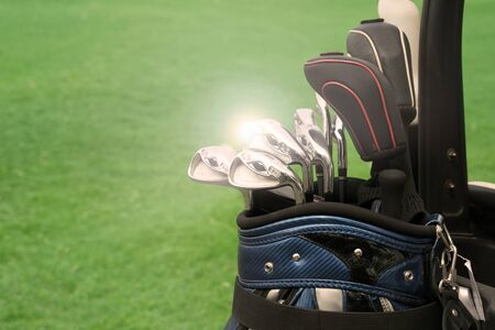conquering adversity: golf club in bag against green grass background