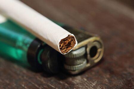 encendedores: cigarrillo y encendedor en la mesa de madera Foto de archivo