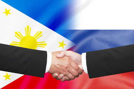 syndicate: two businessman with handshake over half philippines half russian flag