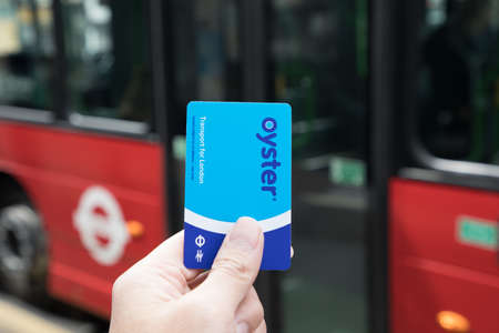 LONDON, ENGLAND - APRIL 30: Hand hold a transport Card with bus background on April 30, 2017 in London England