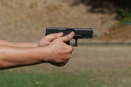 mans hand holding gun with nature background Stock Photo