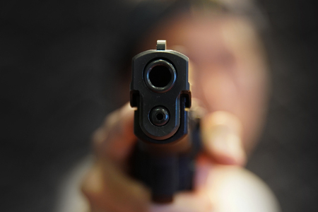 a man hand pointing a gun forward Stock Photo
