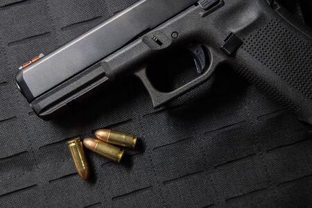 Handgun with bullets on bullet proof vest texture background