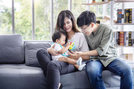 Asian LGBTQ Couple Play with Their Adopted Baby on the Sofa in the Living Room 写真素材