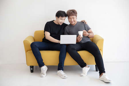 Asian LGBT Gay Couple Using  Laptop Computer Together in the Living Room at Home For Work From Home Concept 写真素材