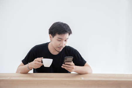 Asian Guy Playing Mobile Phone While Holding a Cup of Coffee in Other Hand with Blank Copy Space