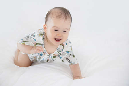 Asian Baby Crawl ing on White Bed 写真素材
