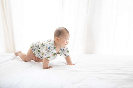 Side View of Asian Baby Crawlng on White Bed