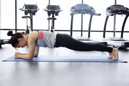 Asian Woman Workout in Planking Pose on a Yoga Mat