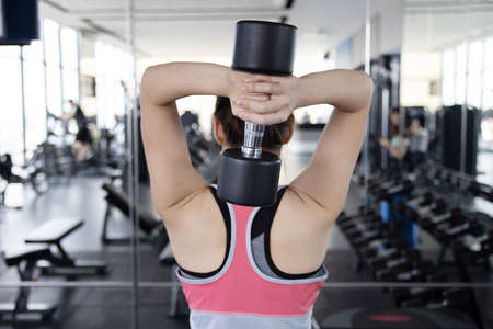 Back View of Asian Woman Exercise her Tricep with Dumbell