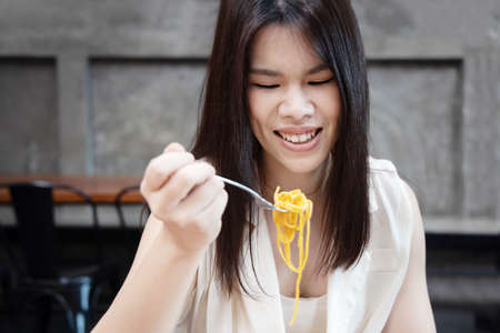 Portrait of Asian Woman Eating Cabonara Spaghetti with a Fork