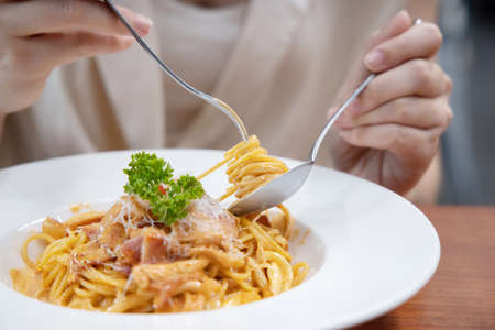 Close-up on Woman Eating Cabonara Spaghetti with a Fork 写真素材