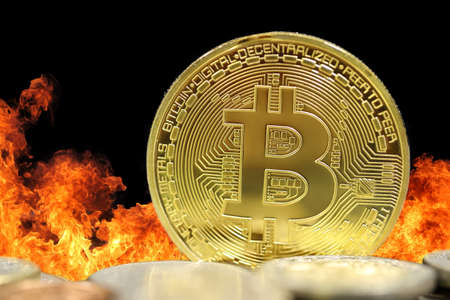 Golden Bitcoin on  Against Fire Background 写真素材