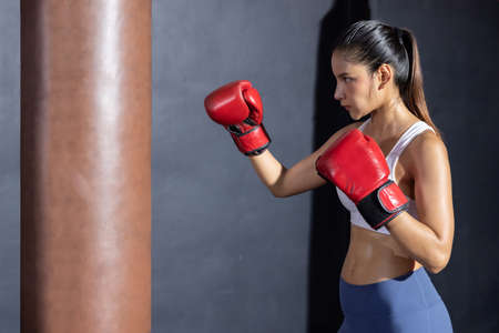 Side View of Asian Woman with Red Boxing Glove  Ready for Boxing Match
