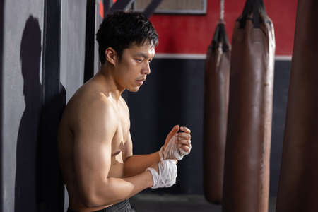 Asian Boxer Wrapping His Hands Before Thai Boxing Training