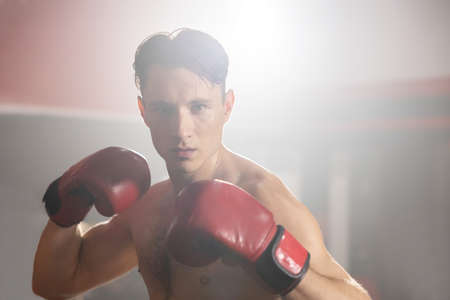 Topless Caucasian Boxer Wearing  Red Boxing Gloves  with  Boxing Pose in Light and Shadow Detting