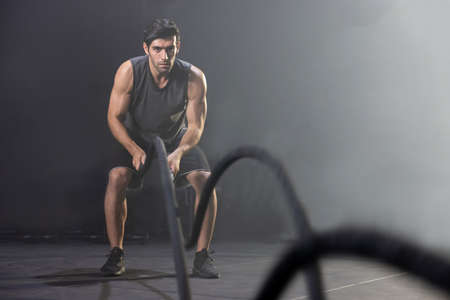 Caucasian Man Using Battle Ropes For Whipping Exercise  in a Gym 写真素材