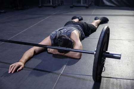 Unconcious Caucasian  Athlete Faint on the Gym Floor with a Barbell in Front of Him 写真素材