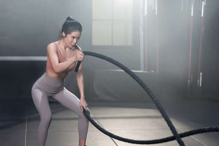 Woman with Battle Ropes Whipping Exercise  in a Gym 写真素材