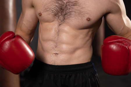 Close up of six pack of male boxer with red gloves