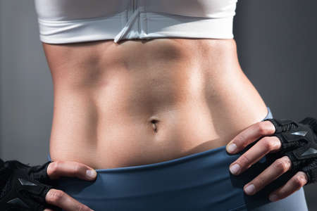 Portrait of Sexy Asian Woman Abdominal with Six Pack Core Body Muscle Against Dark Background 写真素材