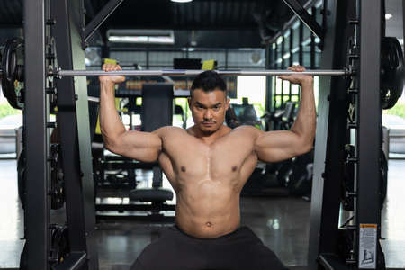 Asian Man Pumping Up Muscles with Weight Lifting Machine in a Gym 写真素材