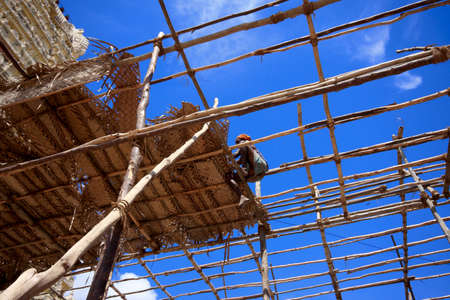 Worker is roofing with leaves. Wooden structure house with blue sky