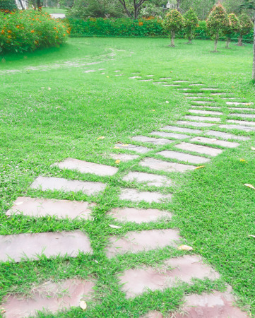 Walking trails, beautiful gardens, paved with stone slabs on the grass green. photo