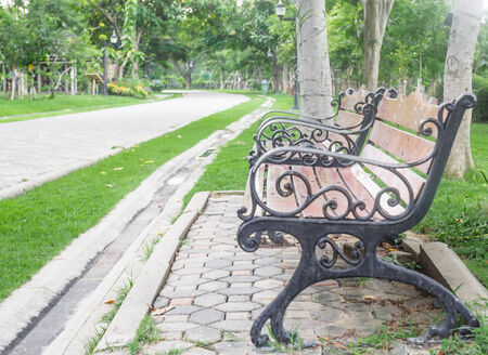 Old wooden bench in the park with jogging road in front. photo