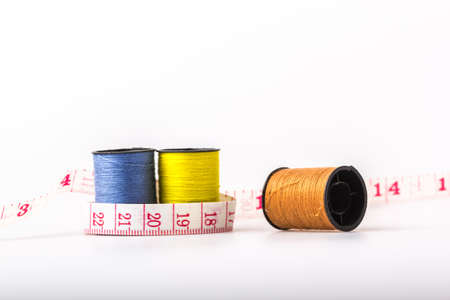 wor: threads and tape measure on a white background.