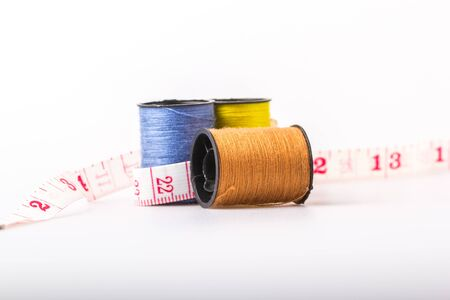 wor: threads and a tape measure on a white background.