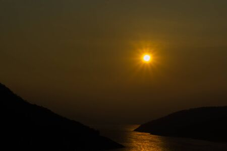 horsetooth rock: The sun was falling during the evening, which is surrounded by mountains with a river in the middle.
