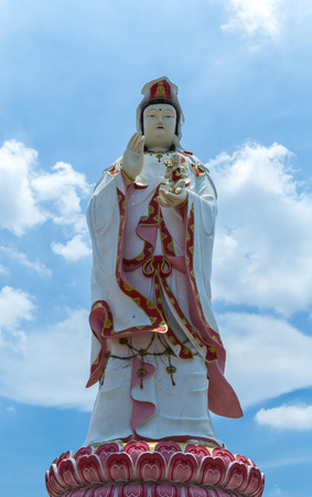 beliefs: The statue of Guanyin That looks white and decorated with beautiful ornaments stands on a lotus base. On the backdrop of the sky God is the one based on the beliefs of the Chinese people.