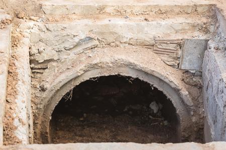 Un vieux tuyau de béton utilisé pour drainer l'eau avec un laitier est déposé dans le drain. Banque d'images - 73452945