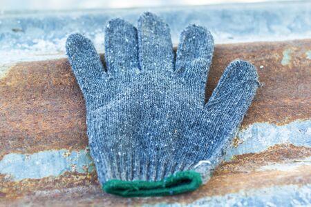 Gants en tissu gris Le vieux est utilisé. Sur la vieille feuille de toiture de zinc rouillée Banque d'images - 74423883