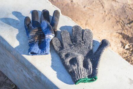 Le vieux gant en tissu est placé sur un poteau en béton par temps ensoleillé. Banque d'images - 74360004