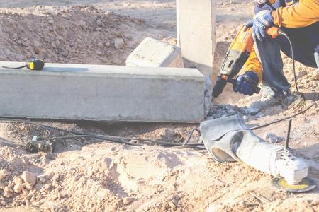 Les litières en béton utilisent une perceuse électrique pour extraire les colonnes de béton jusqu'à la ligne de coupe. Banque d'images - 75070303