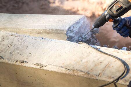 Les litières en béton utilisent une perceuse électrique pour extraire les colonnes de béton jusqu'à la ligne de coupe. Banque d'images - 75074594