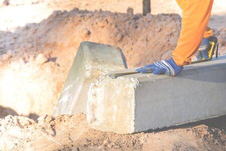 Les techniciens utilisent le compteur pour vérifier la longueur des pôles. Pendant l'impact léger sur le poteau de béton. Banque d'images - 75254643