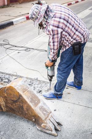 Le technicien utilise une perceuse de route. En forant pour faire vibrer le sol pour améliorer la route. Banque d'images - 77005502