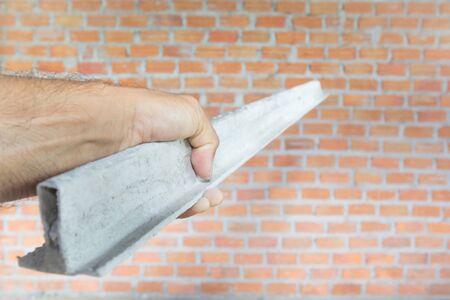 Le bûcheron de béton manipule la ligne de plâtre pointant vers le mur de brique pour commencer à plâtrer le béton. Banque d'images - 78520172