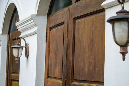 Ancient wooden door in old temple wall with lamp. Thailand photo