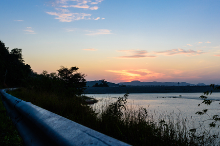 Twilight sky in the morning with silhouette and water in forground. Stock Photo