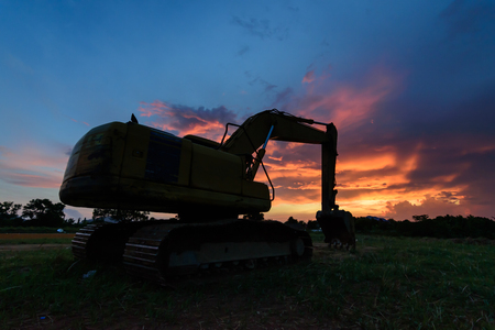 A big excavator earthmoving works on  construction site in Phuket Thailand with twilight sky background.