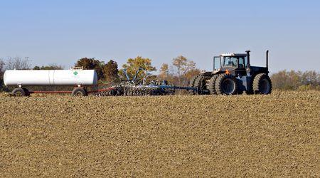 amoniaco: Farm tractor tirando de un arado y una enfermera tanque de amoníaco anhidro fertilizantes  Foto de archivo