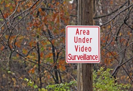 Video surveillance warning sign in a wooded area